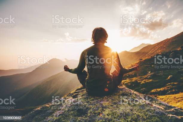 Photo of Man meditating yoga at sunset mountains Travel Lifestyle relaxation emotional concept adventure summer vacations outdoor harmony with nature
