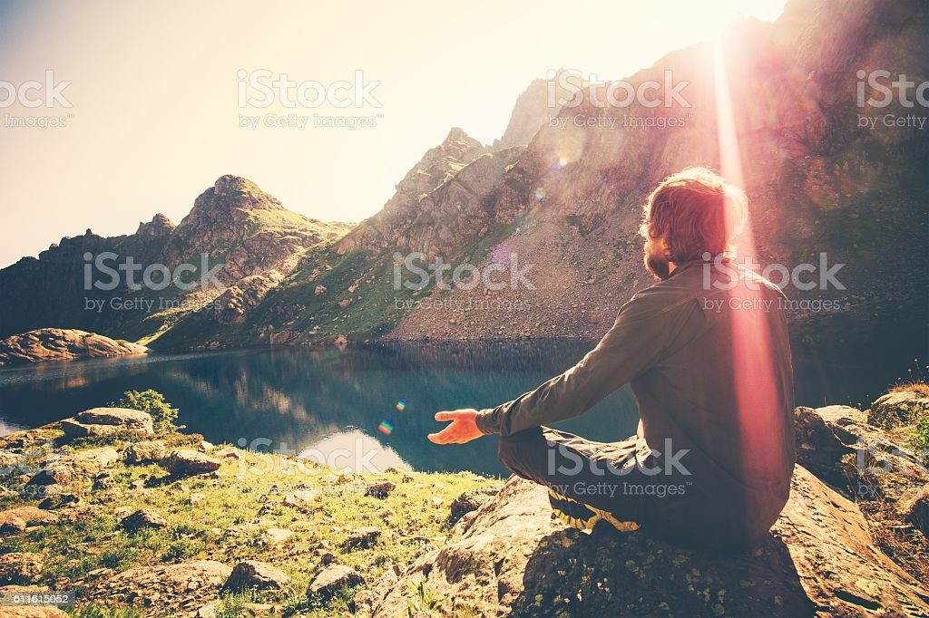 Man meditating yoga relaxing alone sitting lotus pose on stone stock photo