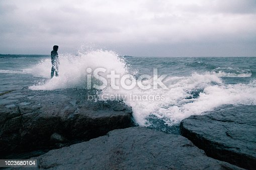 A man standing of the shore of a sea, about to be hit by a big wave.