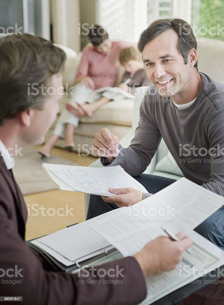 Man meeting with financial advisor in living room stock photo