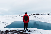 Young man with backpack, in red jacket and black hat exploring the North Iceland and enjoying the view of scenic blue lake in volcano crater and snowcapped mountains