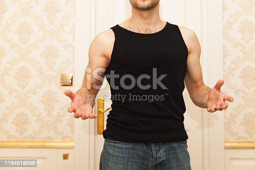 Young brute Caucasian man in black shirt menacingly gesticulates, domestic violence concept