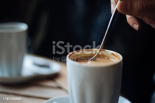 Man mixing a cup of coffee