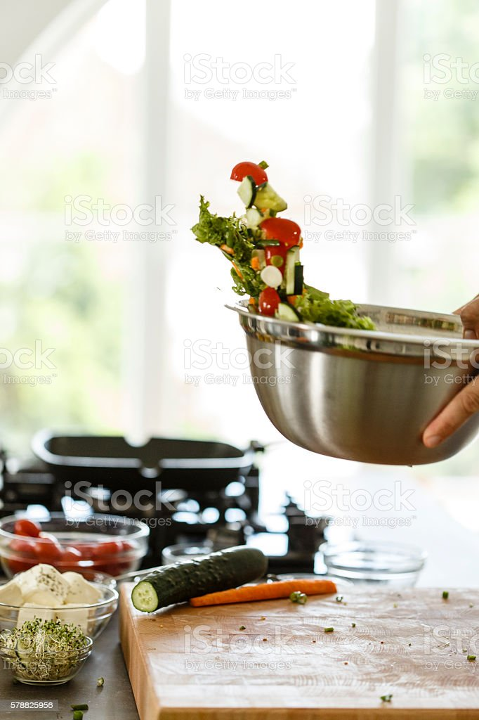 Man mixing vegetables in bowl stock photo