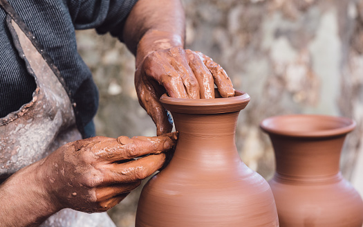 Man molding a clay pot