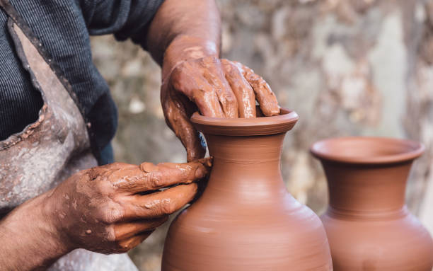 Man molding a clay pot Close up view of an adult male using their own hands to make a ceramic vase. craftsperson stock pictures, royalty-free photos & images
