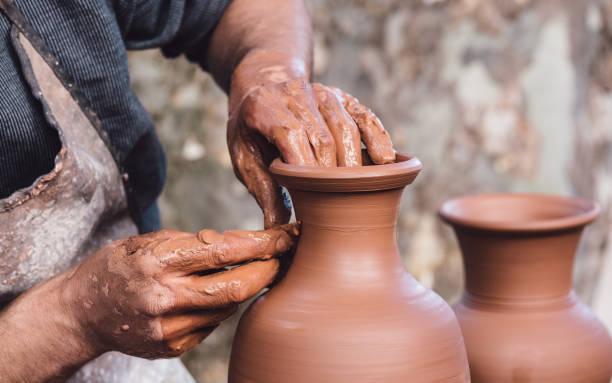 hombre de moldear una vasija de barro - alfarería fotografías e imágenes de stock