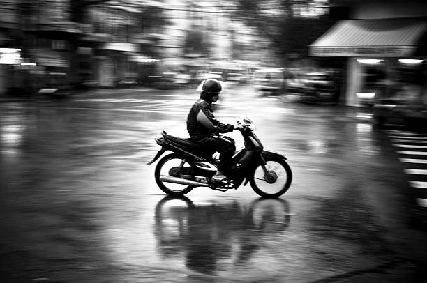 man motorcycling in the rain in nha trang, vietnam - motorbike, umbrella stock pictures, royalty-free photos & images