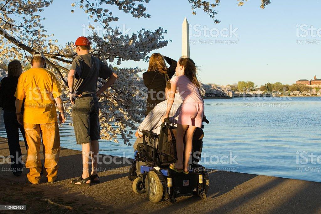 Man Motorized Wheelchair with Granddaughter Riding Along Washington DC royalty-free stock photo