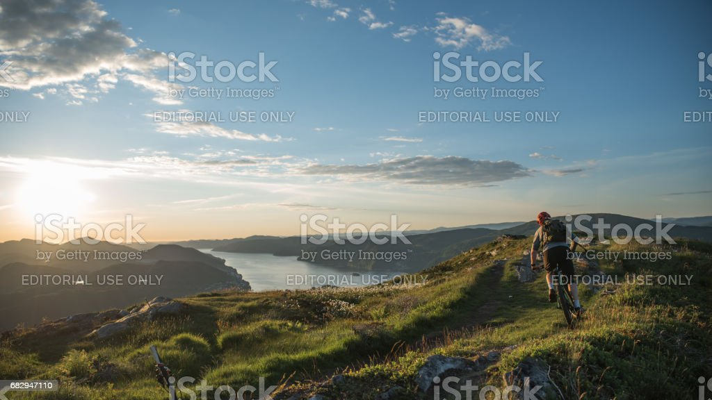 Man mountain biking down towards a fjord during sunset stock photo