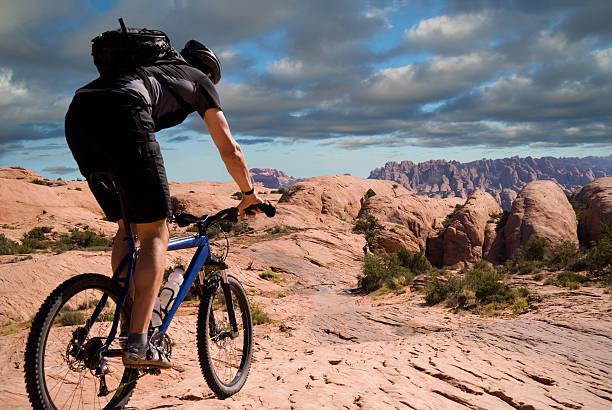 man mountain biking on the slickrock trail in moab, utah - moab utah stockfoto's en -beelden