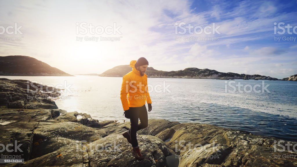 Man mountain hiking by the sea of a fjord in Norway stock photo