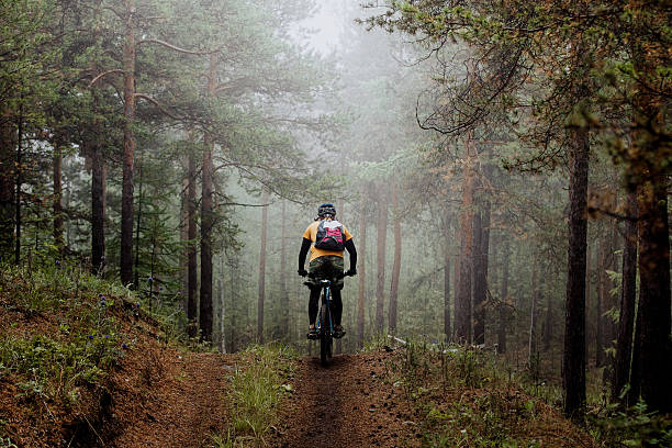 man mountainbiker rides on a sports  bicycle Revda, Russia - July 31, 2016: man mountainbiker rides on a sports  bicycle on a forest trail. in forest mist, mysterious view during Regional competitions on cross-country bike mountain biking stock pictures, royalty-free photos & images