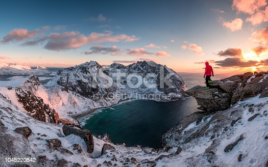 Man mountaineer standing on rock of peak mountain at sunset. Ryten Mountain, Norway