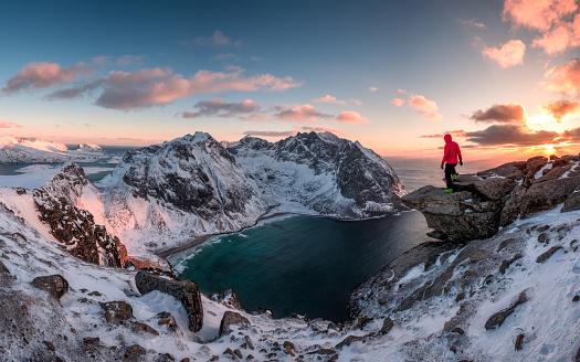 Man mountaineer standing on rock of peak mountain at sunset. Ryten Mountain, Norway