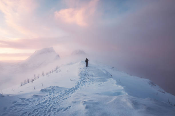 Man mountaineer walking with footprint on snowy mountain and colorful sky in blizzard at sunrise stock photo