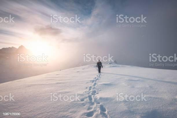 Photo of Man mountaineer walking with snow footprint on peak ridge
