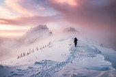 Man mountaineer walking with snow footprint on snow peak ridge in blizzard at morning