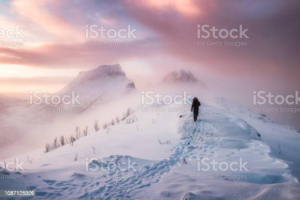 Photo of Man mountaineer walking with snow footprint on snow peak ridge in blizzard