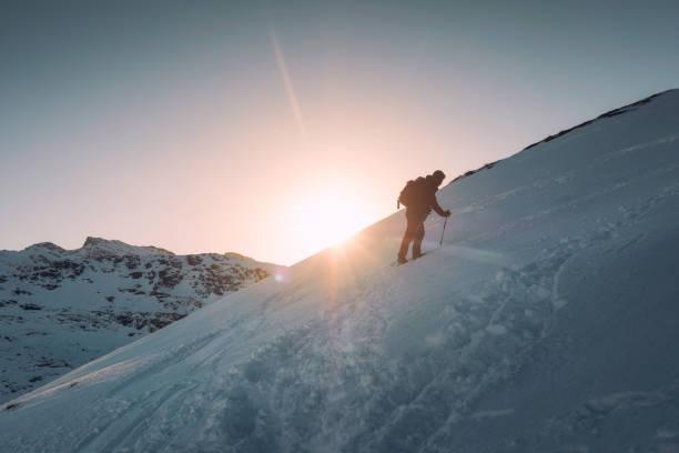 Man mountaineer with trekking pole climbing on snowy hill and sunshine at Ryten mount stock photo
