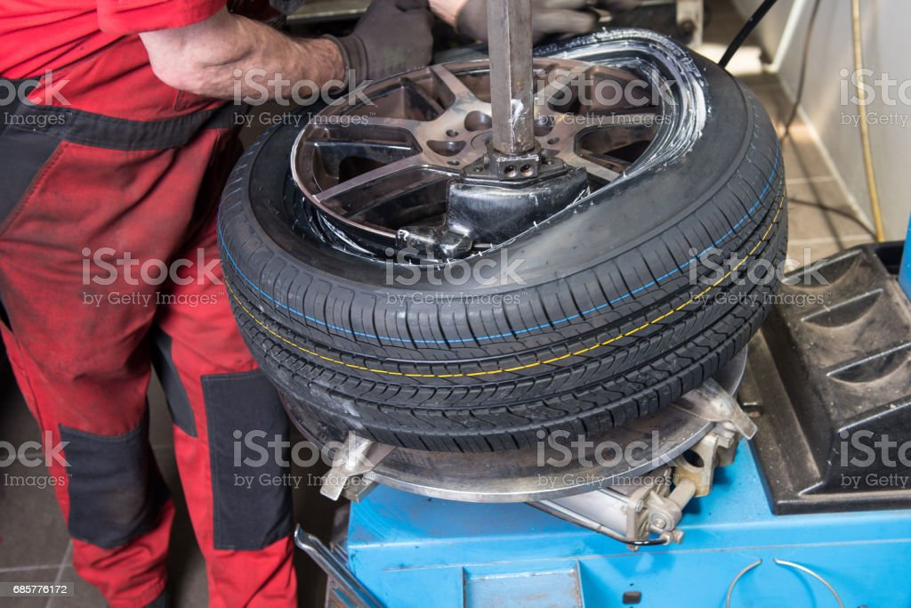 Man mounts new tyre on a rim in the car repair royalty-free stock photo