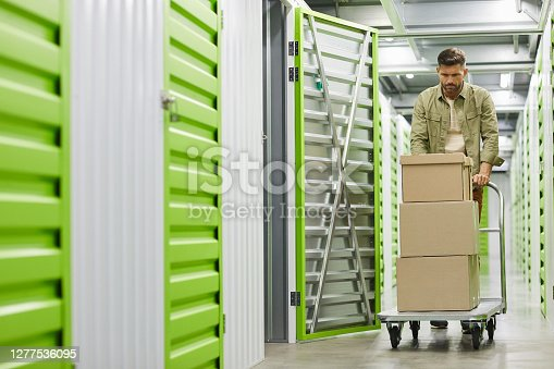 Full length portrait of handsome bearded man loading cart with cardboard boxes into self storage unit, copy space