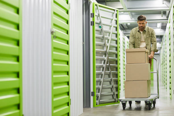 Man Moving Boxes in Self Storage Unit stock photo