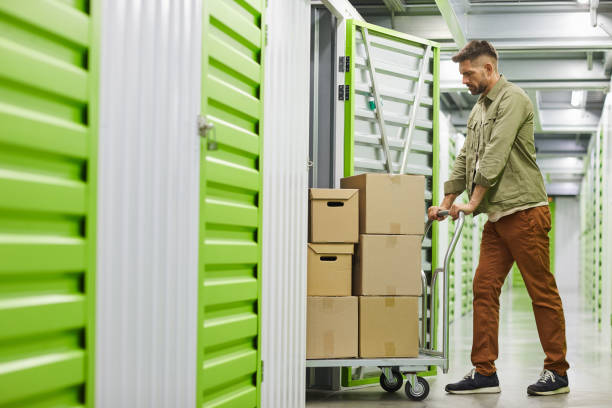 Man Moving Boxes in Storage Unit stock photo