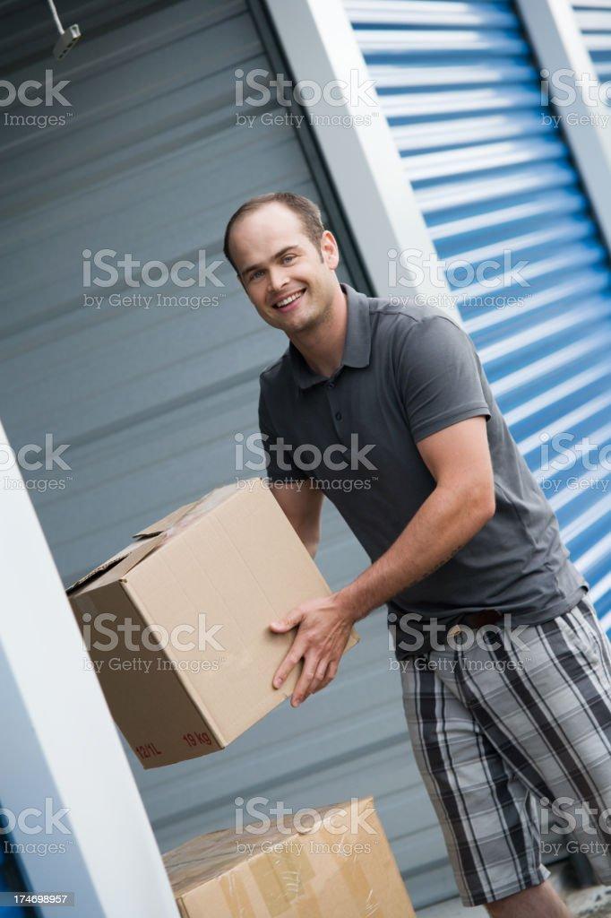 Man Moving Boxes Outside Self Storage Unit stock photo
