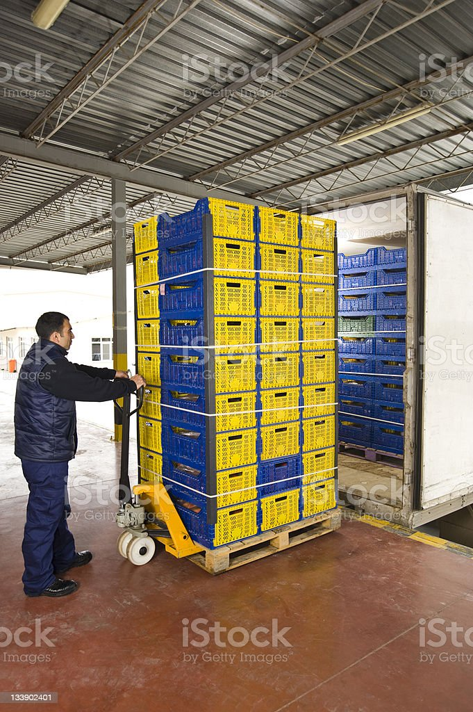 Man moving warehouse shipment on metal trolley stock photo