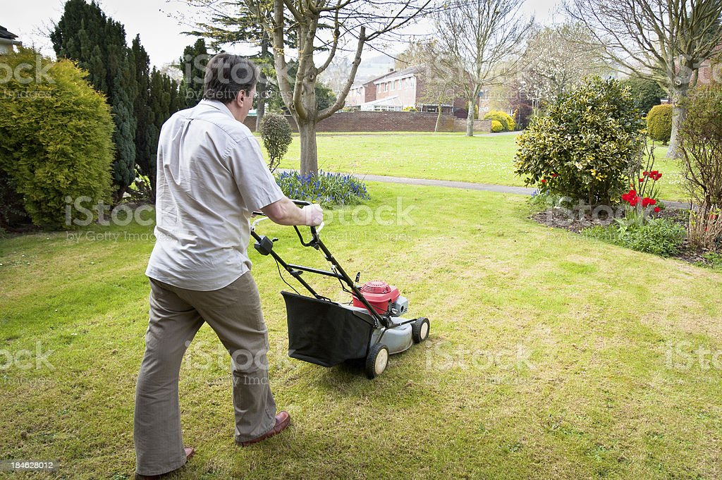 Man Mowing A Grass Lawn With Petrol Lawnmower royalty-free stock photo