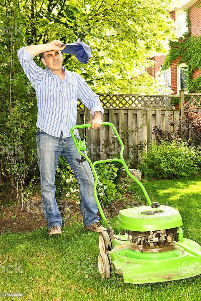 Man mowing a lawn looking tired stock photo