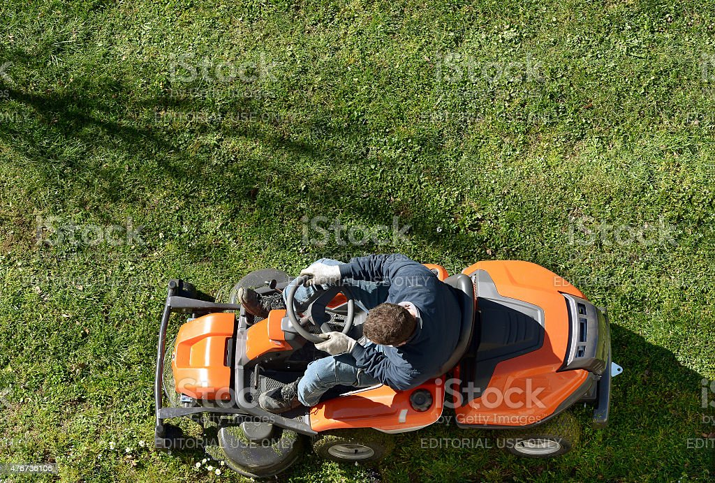 Man mowing a lawn on a ride-on mower stock photo