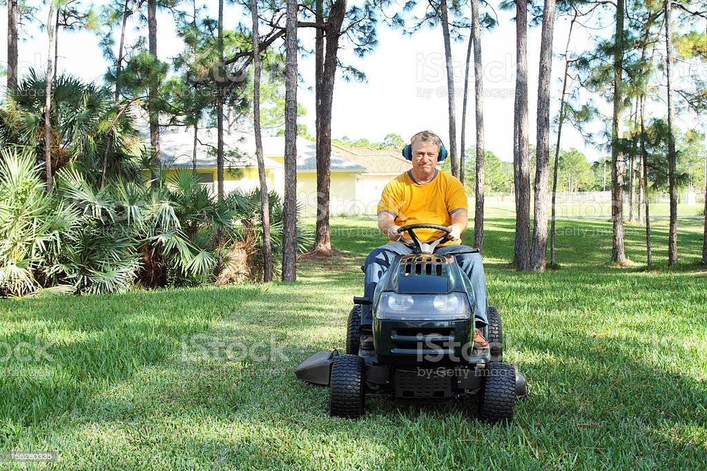 Man mowing grass on riding mower stock photo