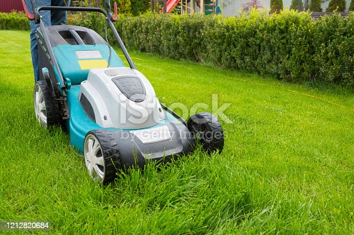 istock A man mowing grass with a lawn mower in the garden on a sunny day. A lawn mower on the lawn, a close-up. 1212820684