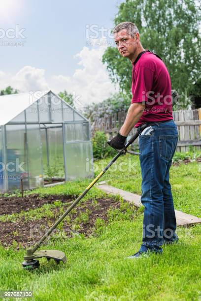Man mowing grass with a trimmer