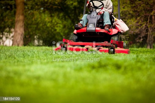 Gardener in the park on a lawn cutting tractor machine