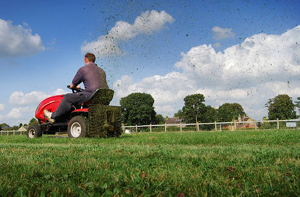 man mowing the grass on a riding mower - riding lawn mower stock photos and pictures