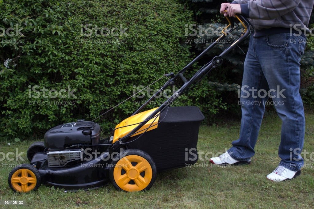 A man mows the grass with a gasoline mower stock photo