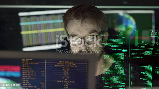 Stock close-up photo of a mature man surrounded by monitors & a holographic display which he is reading.