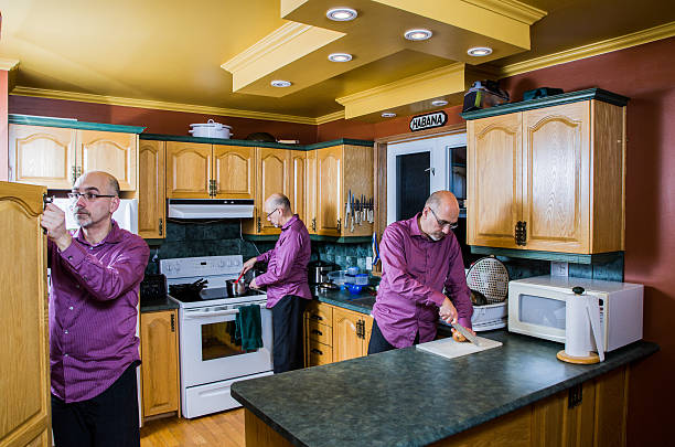 man multi tasking in the kitchen - triplets stock photos and pictures