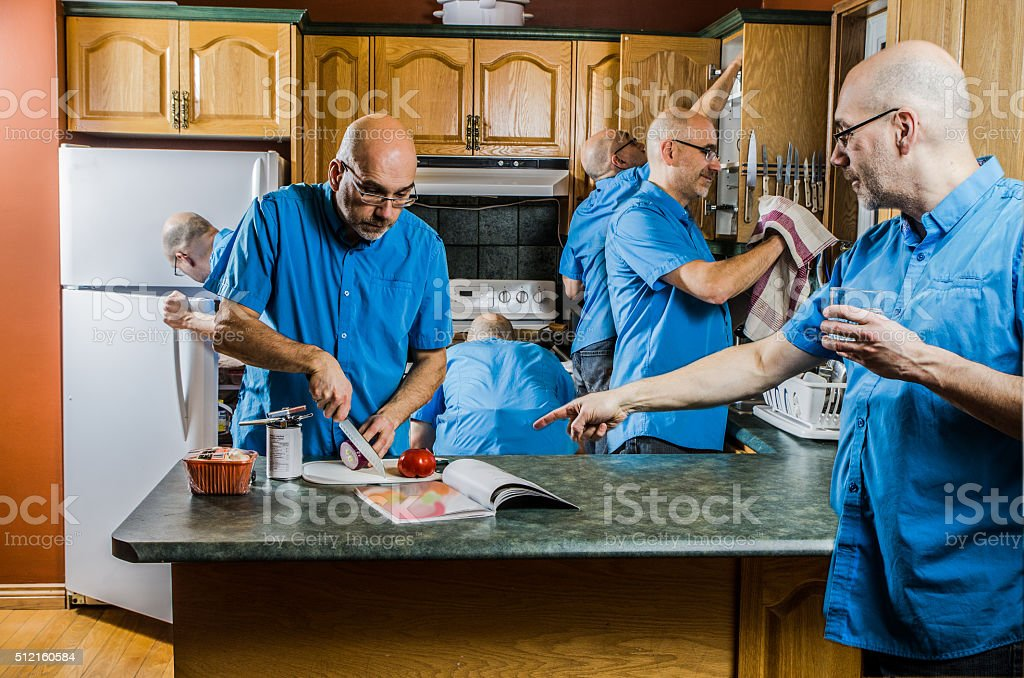 Man multi tasking in the kitchen stock photo