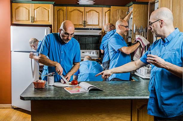 Man multi tasking in the kitchen stock photo