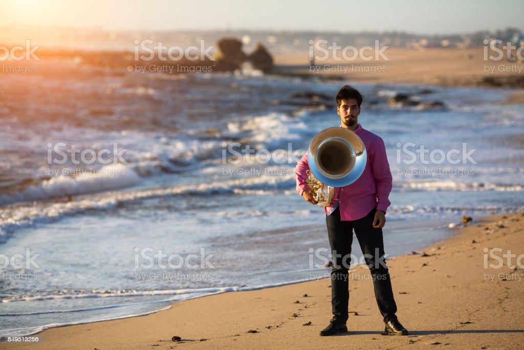 Man musician playing the Tuba on the sea coast. stock photo