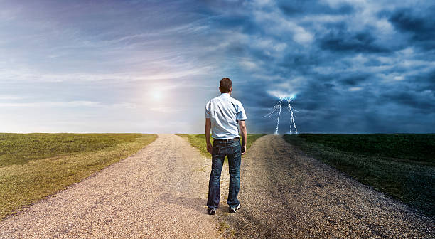 Man must decide his way forward to success or failure Concept of personal decision making. Man stand at a forked road and has to choose his way forward. The one to left is covered in sunlight. The one to the right is dark and lightning is in the horizon. fork stock pictures, royalty-free photos & images