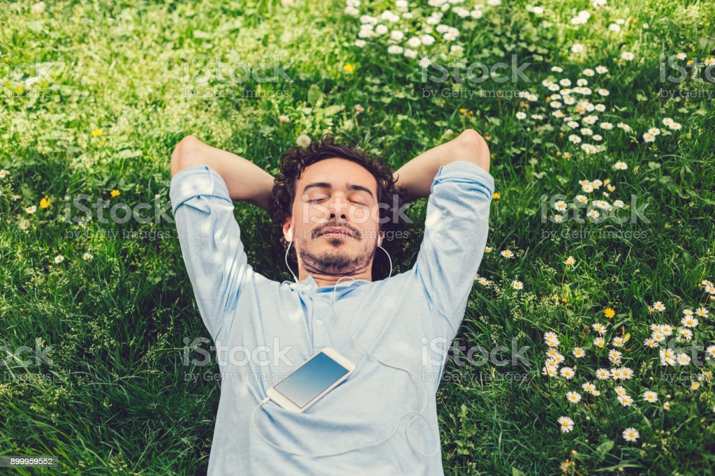 Man napping in the grass Relaxed man lying down at the meadow and listening to music 20-29 Years Stock Photo