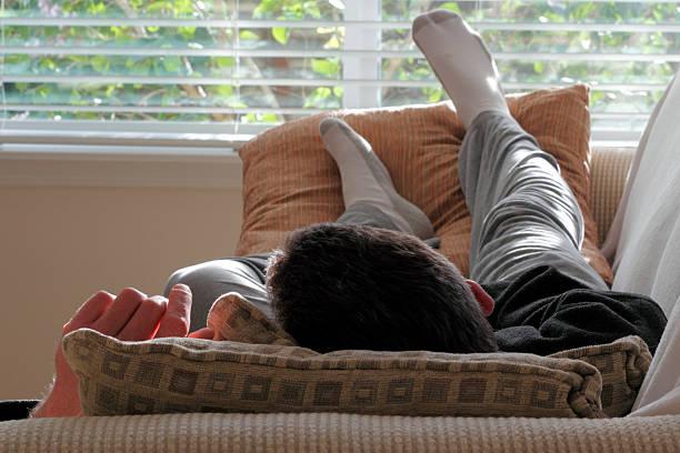 mann nickerchen auf sofa - sweatpants stock-fotos und bilder