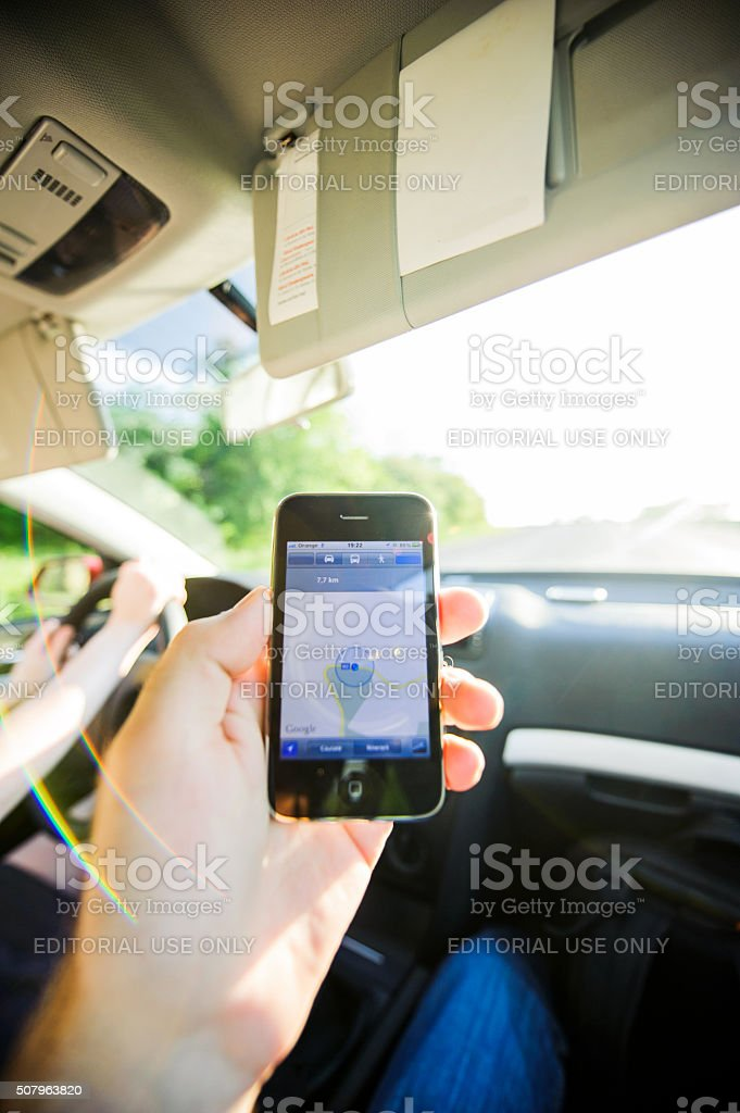 Man holding Apple iPhone smartphone with GPS application inside the...