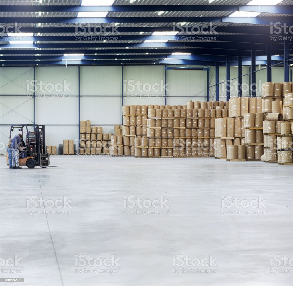 Man Near Forklift in Warehouse with StorageBarrels royalty-free stock photo
