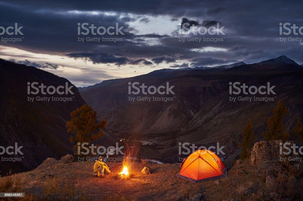 Ein Mann in der Nähe von beleuchteten Zelt und Lagerfeuer in Bergen im Morgengrauen – Foto